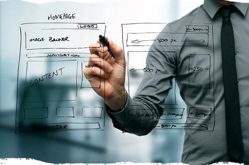 Ejecutivo haciendo boceto de una sitio web en una pizarra de acrílico transparente